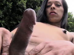Inked up tgirl tugging her ebony cock